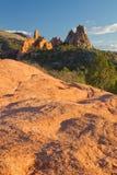 Roter Felsenvordergrund mit Garten der Götter im Hintergrund Stockfotos