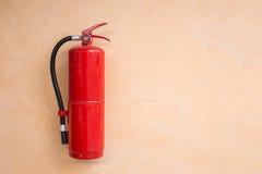 Roter Feuerlöscherbehälter auf orange Wand Lizenzfreie Stockbilder