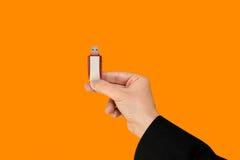 Roter Flash-Speicher an Hand mit lokalisiertem orange Hintergrund Stockfotos