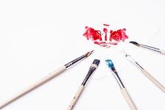 Roter Fleck und Pinsel auf einem weißen Hintergrund Stockfotos