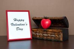 Roter Fotorahmen und geöffneter dekorativer Kasten mit Herzen auf Holztisch Lizenzfreie Stockfotografie