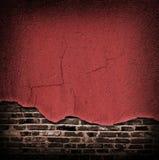 Roter gebrochener rauer Gips, der weg die Backsteinmauer kommt Stockfoto