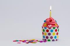 Roter Geburtstagskleiner kuchen mit brennender Kerze Lizenzfreie Stockbilder