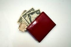 Roter Geldbeutel mit Geld auf einem weißen Hintergrund lizenzfreies stockbild