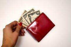Roter Geldbeutel mit Geld auf einem weißen Hintergrund stockfotos