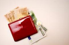 Roter Geldbeutel mit Geld auf einem weißen Hintergrund stockfotografie
