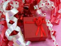 Roter Geschenk-Kasten mit lockigen Farbbändern Stockfotos