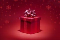 Roter Geschenkkasten auf rotem Hintergrund mit Schneefällen Lizenzfreie Stockfotografie