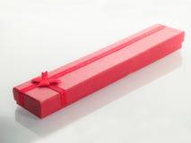 Roter Geschenkkasten mit rotem Farbband Stockfotos
