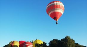 Roter gestreifter Ballon im blauer Himmel wuth Wald im Abstieg Stockfotografie