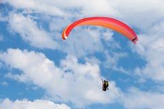 Roter Gleitschirm im blauen Himmel mit Wolken Stockfotos