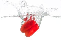 Pfeffer, der im Wasser spritzt Lizenzfreie Stockfotografie