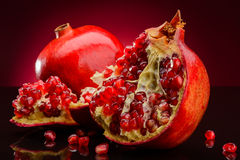 Roter Granatapfel auf dunklem Hintergrund Stockbild