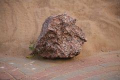 Roter Granit und Sand des großen Steinbruchsteins, die an gepflastert mit farbigem Betonblockfußgängerbereich kommt Lizenzfreie Stockfotografie