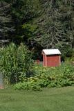 Roter hölzerner Erzeugnis-Stand und Garten Stockfotos