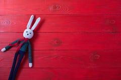 Roter hölzerner Hintergrund für Ihr Design Ein Spielzeug ist ein Hase, der in der Technik von amigurumi gestrickt wird lizenzfreie stockfotos