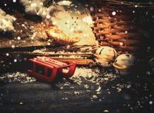 Roter hölzerner Schlitten und Weihnachtsdekoration, Korb, Kiefern-Kegel und Glaskugeln auf rustikalem hölzernem Hintergrund Lizenzfreie Stockfotos