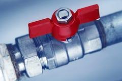 Roter Hahn auf Metallwasserleitung stockfotos