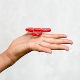 Roter Handspinner Junge, der einen populären Spielzeugunruhespinner in seiner Hand spielt Entspannung Antidruck und Entspannung a Stockbild