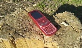 Roter Handy 2000s steht auf einem hölzernen Stumpf still Lizenzfreies Stockbild