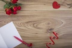 Roter heart-shaped Schmucksachegeschenkkasten und eine rote Spule auf einem Zeichen Lizenzfreie Stockbilder