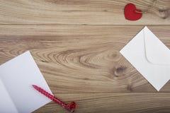 Roter heart-shaped Schmucksachegeschenkkasten und eine rote Spule auf einem Zeichen Lizenzfreies Stockbild