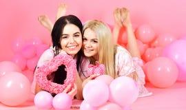 Roter heart-shaped Schmucksachegeschenkkasten und eine rote Spule auf einem Zeichen Schwestern, Freunde in den Pyjamas an der Pyj Stockfoto