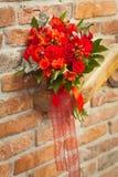 roter Heiratsblumenstrauß auf einem Ziegelsteinhintergrund stockfotografie