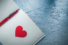Roter Herz Biro-Stiftnotizblock auf der metallischen Hintergrundbildung conc lizenzfreie stockfotos