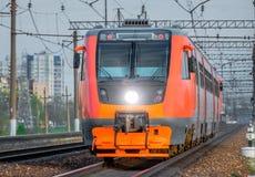 Roter HochgeschwindigkeitsPersonenzug, der durch die Eisenbahn hetzt lizenzfreie stockbilder
