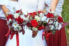Roter Hochzeitsblumenstrauß in ihren Händen lizenzfreie stockbilder