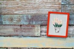 Roter Holzrahmen, der an einem hölzernen Brett hängt Stockbild