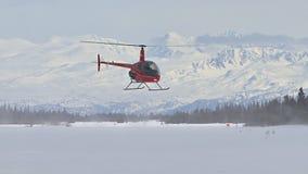 Roter Hubschrauber, der über schneebedecktem Boden schwebt stock video