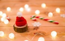 Roter Hut auf einem Stück Holz in den Lichtern und in der Zuckerstange lizenzfreie stockfotos