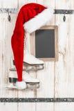 Roter Hut für Santa Claus und weiße Schlittschuhe Weinleseweihnachten Stockfotos