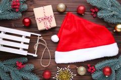 Roter Hut und Geschenke Santa Clauss auf grauem Hintergrund neue Ideen, das Haus zu verzieren dieses Weihnachten lizenzfreie stockfotografie
