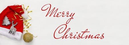 Roter Hut Weihnachtsmanns nahe bei hölzernen Dekorationen lizenzfreie stockbilder