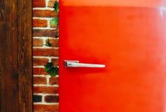 Roter Kühlschrank der Retro- Weinleseart gegen Backsteinmauerhintergrund lizenzfreie stockfotos