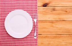 Roter karierter Tischdeckenschottenstoff des Tischbestecks auf Draufsicht des Holztischs Lizenzfreie Stockbilder