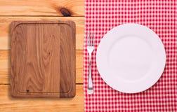 Roter karierter Tischdeckenschottenstoff des Tischbestecks auf hölzernem Stockfotos