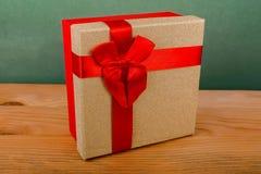 roter Kasten für Weihnachtsgeschenke auf einem grünen Hintergrund, Weihnachtsgeschenke, rotes Band, roter Bogen Lizenzfreies Stockbild