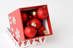 Roter Kasten mit Weihnachtsdekoration auf weißem Hintergrund Lizenzfreie Stockfotos