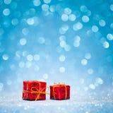 Roter Kasten mit Weihnachtsgeschenk auf glänzendem Funkelnblau Lizenzfreie Stockbilder