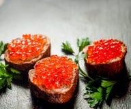 Roter Kaviar auf Brot auf Schieferhintergrund lizenzfreie stockfotografie