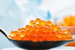 Roter Kaviar auf Makrostillleben des Retro- Löffels auf blauem Hintergrund Lizenzfreie Stockfotografie