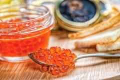 Roter Kaviar und Kaviar Löffel des roten Kaviars und der offenen Dosen cavi lizenzfreie stockbilder