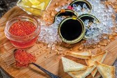 Roter Kaviar und Kaviar Löffel des roten Kaviars und der offenen Dosen cavi stockbilder