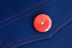 Roter Knopf auf blauem Gewebe Stockfotografie
