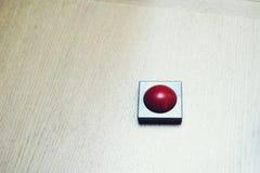 roter Knopf auf hölzerner Tabelle Lizenzfreies Stockfoto