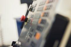 Roter Knopf des Metalls der Bedienfeldmaschinellen bearbeitung, industrieller Hintergrund Stockbilder